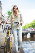 Dutch woman with bicycle in amsterdam walking