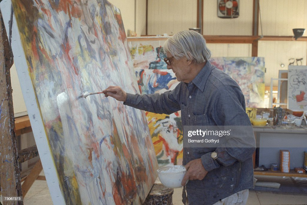 Dutch-born American abstract expressionist painter Willem de Kooning (1904 - 1997) paints on a canvas in his studio, Springs, Long Island, New York, 1980.