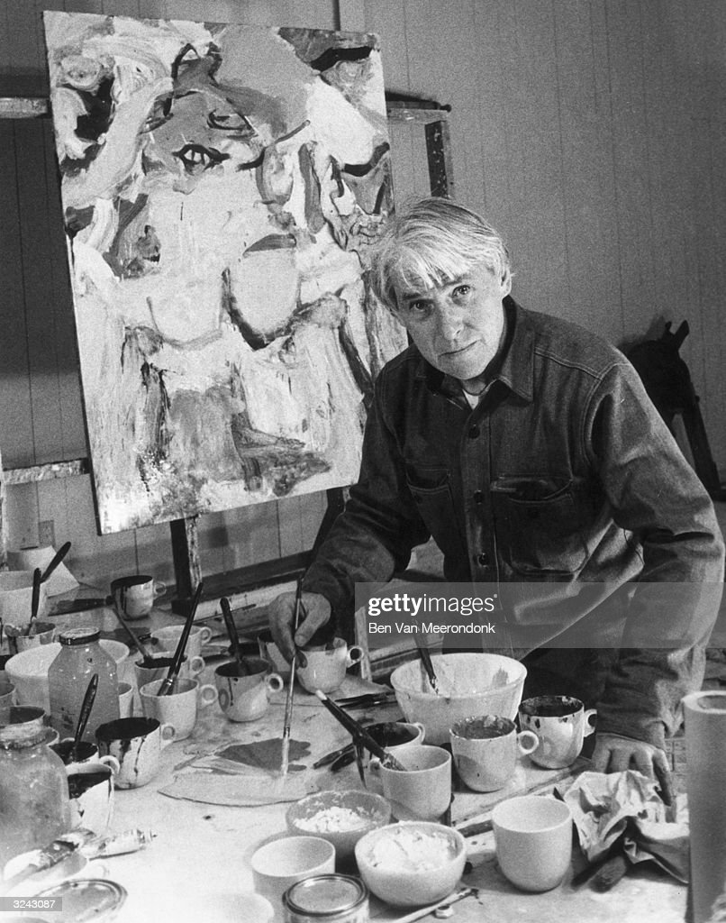 Dutch-born painter Willem de Kooning (1904-1997) looks at the camera as he mixes paint on a large workbench, painting a canvas in his studio in Easthampton, Long Island, New York.