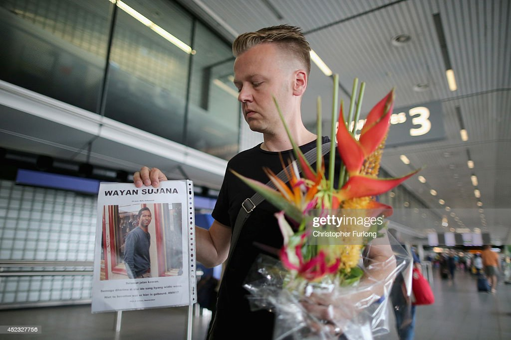 Dutchman Arthur Laumann holds a floral tribute and photograph of family friend Wayan Sujana of Bali, believed to be missing on Malaysia Airlines flight MH17, is fixed to the ticketing desk of Malaysia Airlines at Schiphol Airport on July 18, 2014 in Amsterdam, Netherlands. Malaysia Airlines flight MH17 travelling from Amsterdam to Kuala Lumpur crashed yesterday on the Ukraine/Russia border near the town of Shaktersk. The Boeing 777 was carrying 298 people including crew members, the majority of the passengers being Dutch nationals, believed to be at least 173, 44 Malaysians, 27 Australians, 12 Indonesians and 9 Britons. It has been speculated that the passenger aircraft was shot down by a surface to air missile by warring factions in the region. (Photo by Christopher Furlong/Getty Images)ce to air missile by warring factions in the region.