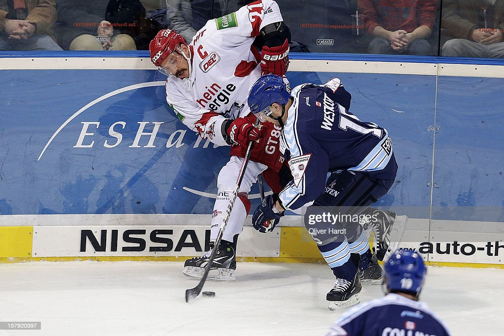 Duvie Westsott (R) of Hamburg battles for the puck with <a gi-track='captionPersonalityLinkClicked' href=/galleries/search?phrase=John+Tripp&family=editorial&specificpeople=215311 ng-click='$event.stopPropagation()'>John Tripp</a> (L) of Cologne during the DEL 1 Bundesliga match between Hamburg and Cologne at O2 World on December 7, 2012 in Hamburg, Germany.