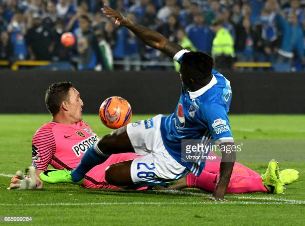 Duvier Riascos of Millonarios vies for the ball with Franco Armani goalkeeper of Atletico Nacional during the match between Millonarios and Atletico...