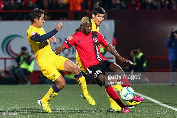 Duvier Riascos of Tijuana struggles for the ball with Adrian Aldrete and Francisco Javier Rodriguez of America during the match between Tijuana and...