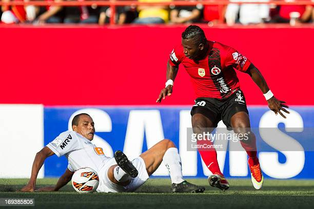 Duvier Riascos of Xolos fights for the ball with Gilberto Silva of Atletico Mineiro during a match between Xolos and Atletico Mineiro as part of the...