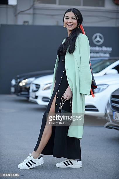 Duygu Senyurek poses wearing dress by Trendyol scarf by Tukutukum shoes by Adidas and hand bag by Chanel during Mercedes Benz Fashion Week Istanbul...