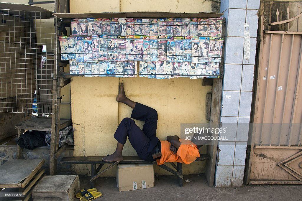 A dvd vendor takes a nap at a local market in Bamako on March 6, 2013. AFP PHOTO / JOHN MACDOUGALL
