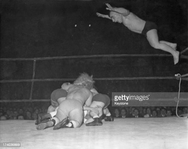 A 'dwarf catching' match at the Palais des Sports in Paris France 29th January 1957 Buried under the wrestlers is the unfortunate referee Meanwhile...