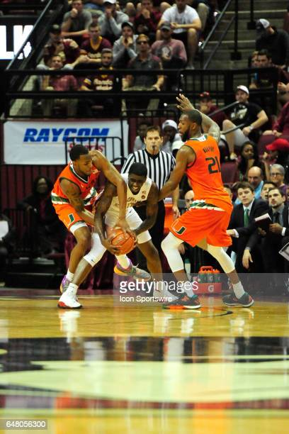 Dwayne Bacon guard Florida State University Seminoles takes Dewan Huell forward Miami Hurricanes across the hip for a jump ball in an Atlantic Coast...