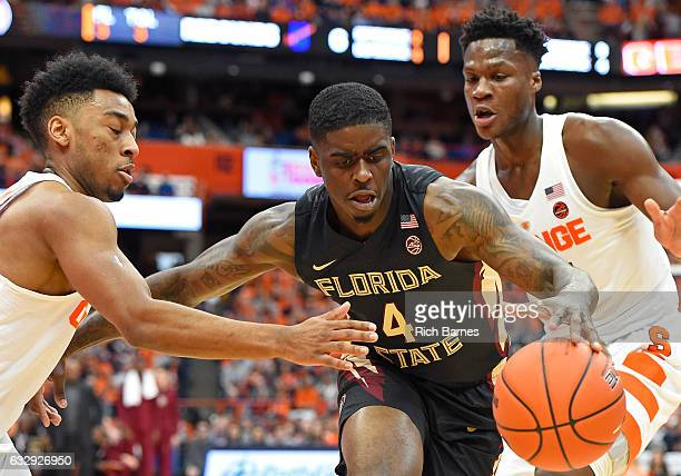 Dwayne Bacon of the Florida State Seminoles reaches for a loose ball between the defense of John Gillon and Tyler Roberson of the Syracuse Orange...