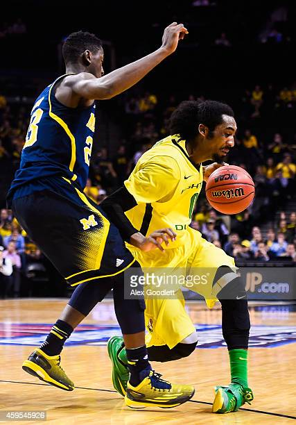 Dwayne Benjamin of the Oregon Ducks rolls his ankle under Caris LeVert of the Michigan Wolverines in the second half at the Barclays Center on...
