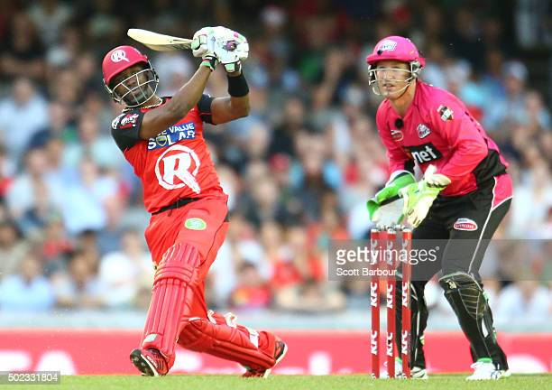 Dwayne Bravo of the Renegades hits a six as wicketkeeper Brad Haddin of the Sixers looks on during the Big Bash League match between the Melbourne...