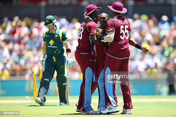 Dwayne Bravo of the West Indies celebrates the wicket of Michael Clarke of Australia with Darren Sammy and Kieron Pollard during game two of the...