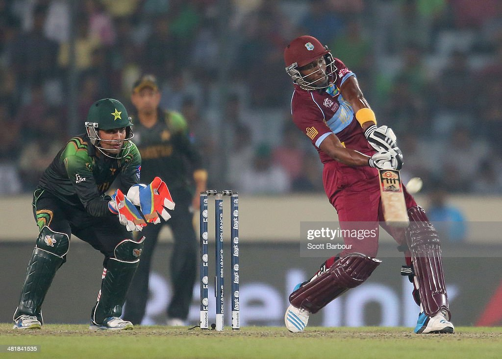 <a gi-track='captionPersonalityLinkClicked' href=/galleries/search?phrase=Dwayne+Bravo&family=editorial&specificpeople=178945 ng-click='$event.stopPropagation()'>Dwayne Bravo</a> of the West Indies hits a six as <a gi-track='captionPersonalityLinkClicked' href=/galleries/search?phrase=Kamran+Akmal&family=editorial&specificpeople=221679 ng-click='$event.stopPropagation()'>Kamran Akmal</a> of Pakistan looks on during the ICC World Twenty20 Bangladesh 2014 match between West Indies and Pakistan at Sher-e-Bangla Mirpur Stadium on April 1, 2014 in Dhaka, Bangladesh.