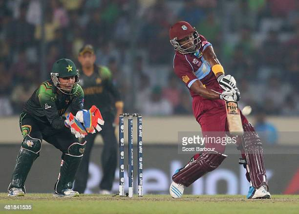 Dwayne Bravo of the West Indies hits a six as Kamran Akmal of Pakistan looks on during the ICC World Twenty20 Bangladesh 2014 match between West...