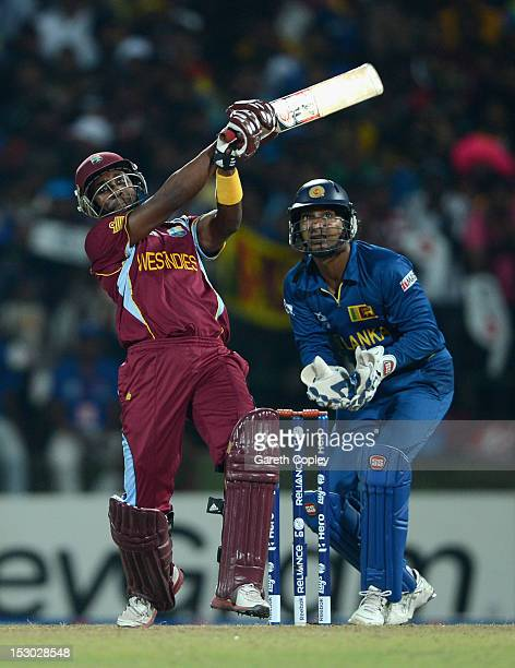 Dwayne Bravo of the West Indies hits out for six runs watched by Sri Lanka wicketkeeper Kumar Sangakkara during the ICC World Twenty20 2012 Super...