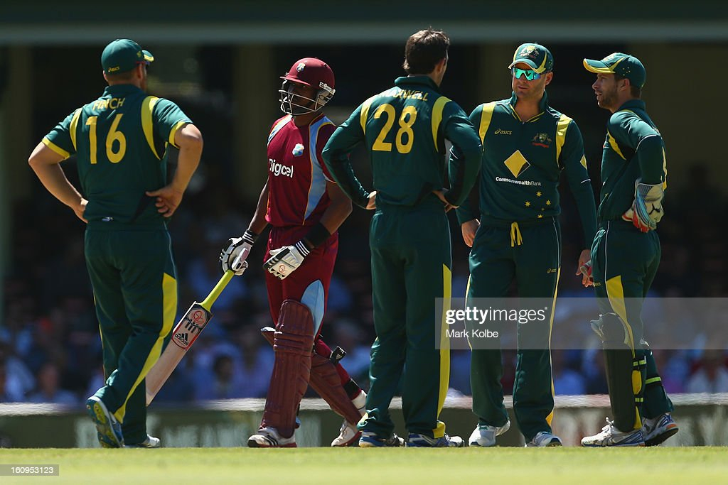 Dwayne Bravo of the West Indies walks past as Glenn Maxwell, Michael Clarke and Matthew Wade of Australia decided whether to use the DRS during game four of the Commonwealth Bank One Day International Series between Australia and the West Indies at Sydney Cricket Ground on February 8, 2013 in Sydney, Australia.