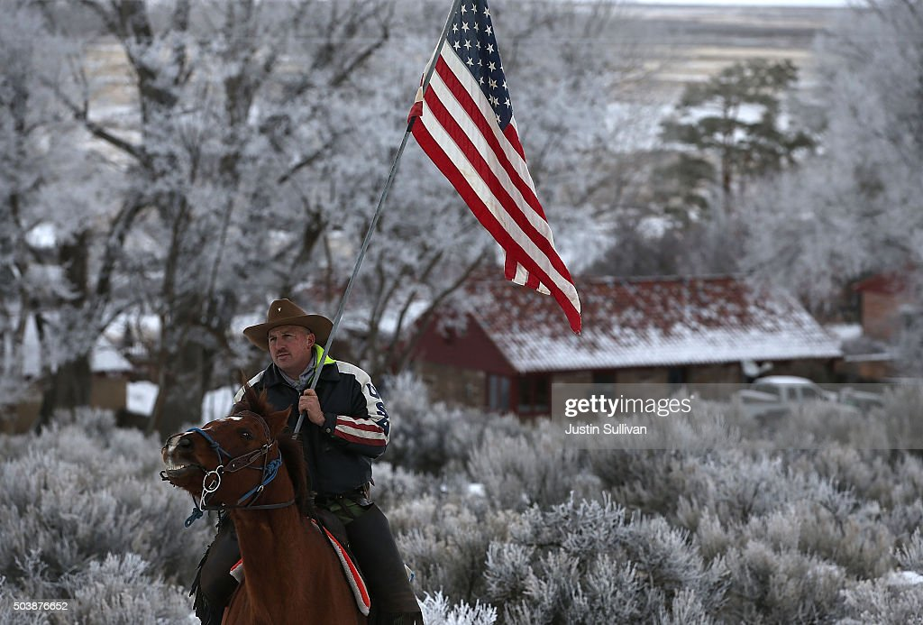 Dwayne Ehmer carries an American flag as he rides his horse on the Malheur National Wildlife Refuge on January 7 2016 near Burns Oregon An armed...