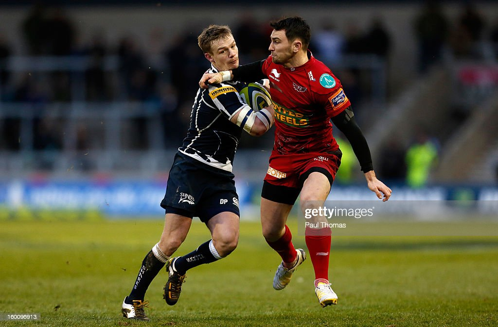 Dwayne Peel (L) of Sale Sharks in action with Kristian Phillips of Scarlets during the LV= Cup match between Sale Sharks and Scarlets at Salford City Stadium on January 26, 2013 in Salford, England.