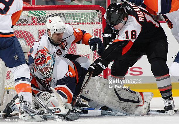 Dwayne Roloson and Doug Weight of the New York Islanders defend against the attack of Mike Richards of the Philadelphia Flyers on March 9 2010 at the...