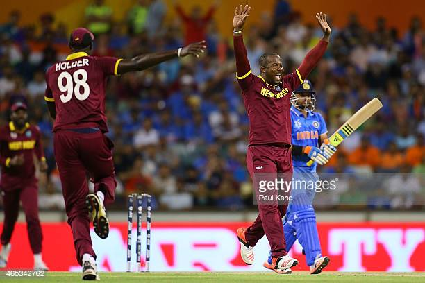 Dwayne Smith of the West Indies celebrates the wicket of Suresh Raina of India during the 2015 ICC Cricket World Cup match between India and the West...