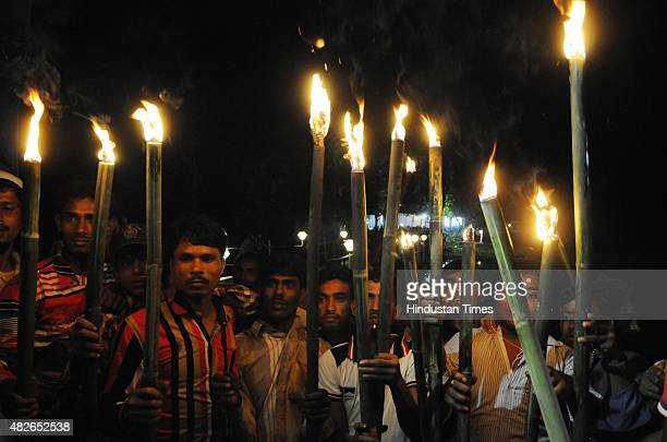 Dwellers light torches at Madhya Mashaldanga enclave Cooch Behar during the zero hour celebration on August 1 2015 in Cooch Behar India Historic...