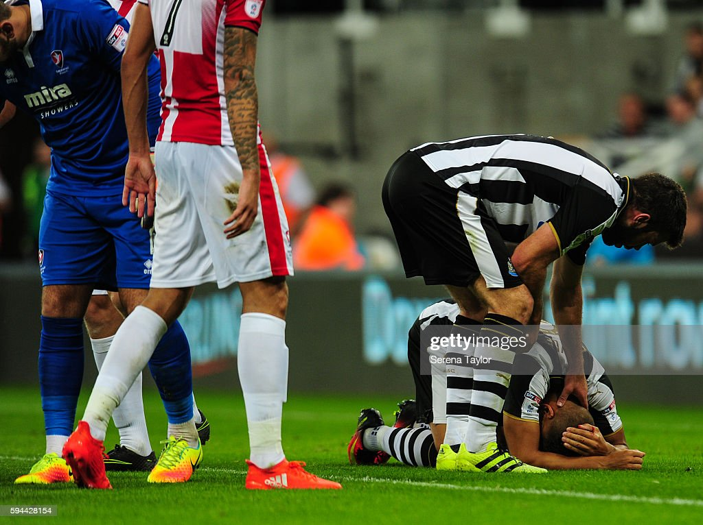 Dwight Gale of Newcastle United holds his head whilst being comforted by teammate Grant Hanley after receiving a head injury during the EFL cup...