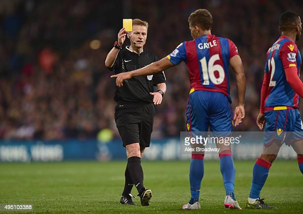 Dwight Gayle of Crystal Palace is shown a yellow card by referee Mike Jones during the Barclays Premier League match between Crystal Palace and...