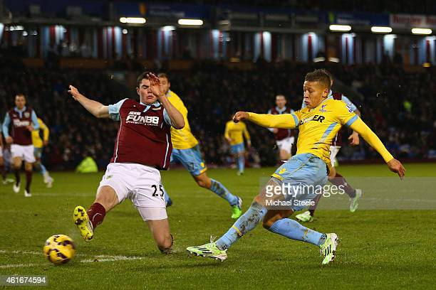 Dwight Gayle of Crystal Palace socres their third goal under pressure from Michael Keane of Burnley during the Barclays Premier League match between...