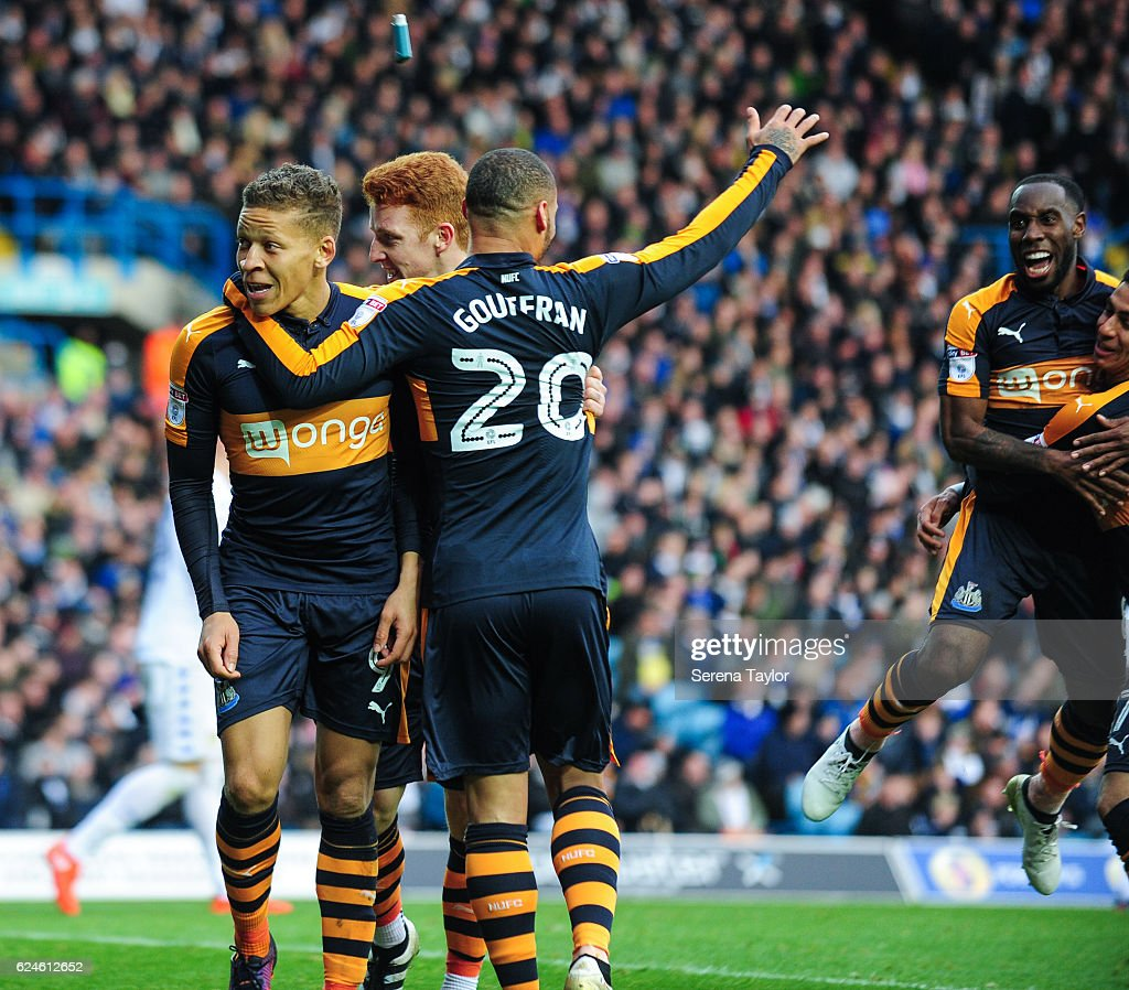 Dwight Gayle of Newcastle (L) smiles with teammates Jack Colback (C) and Yoan Gouffran (R) after an inhaler is thrown at him after he scored Newcastle's second goal during the Sky Bet Championship Match between Leeds United and Newcastle United at Elland Road on November 20, 2016 in London, England.