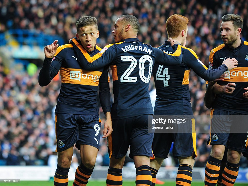 Dwight Gayle of Newcastle United (L) celebrates with teammates Paul Dummett (R) Jack Colback (second from R) and Yoan Gouffran (C) after a fan throws an inhaler at him after he scored Newcastle's second goal during the Sky Bet Championship Match between Leeds United and Newcastle United at Elland Road on November 20, 2016 in London, England.