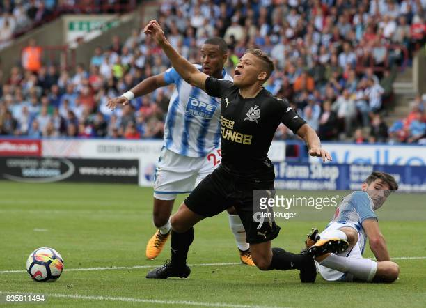 Dwight Gayle of Newcastle United is fouled by Christopher Schindler of Huddersfield Town in the area during the Premier League match between...
