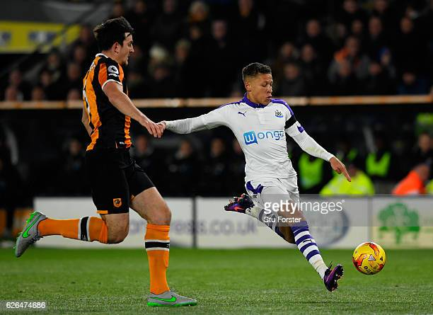 Dwight Gayle of Newcastle United shoots as Harry Maguire of Hull City move in during the EFL Cup QuarterFinal match between Hull City and Newcastle...