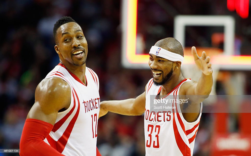 Dwight Howard #12 (L) and Corey Brewer #33 of the Houston Rockets celebrate a three-point basket during their game against the Miami Heat at the Toyota Center on January 3, 2015 in Houston, Texas.