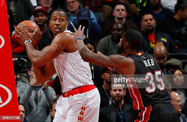 Dwight Howard of the Atlanta Hawks grabs a rebound against Willie Reed of the Miami Heat at Philips Arena on December 7 2016 in Atlanta Georgia NOTE...