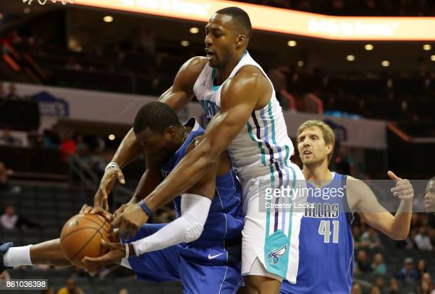 Dwight Howard of the Charlotte Hornets goes after a ball against Harrison Barnes as teammate Dirk Nowitzki of the Dallas Mavericks watches on during...
