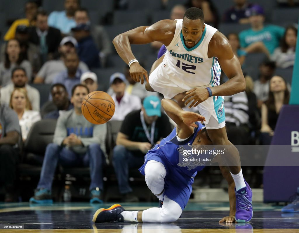Dwight Howard #12 of the Charlotte Hornets goes after a loose ball against Devin Harris #34 of the Dallas Mavericks during their game at Spectrum Center on October 13, 2017 in Charlotte, North Carolina.