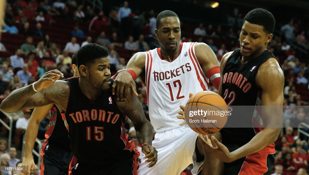 <a gi-track='captionPersonalityLinkClicked' href=/galleries/search?phrase=Dwight+Howard&family=editorial&specificpeople=201570 ng-click='$event.stopPropagation()'>Dwight Howard</a> #12 of the Houston Rockets battles for the ball with <a gi-track='captionPersonalityLinkClicked' href=/galleries/search?phrase=Amir+Johnson&family=editorial&specificpeople=556786 ng-click='$event.stopPropagation()'>Amir Johnson</a> #15 and <a gi-track='captionPersonalityLinkClicked' href=/galleries/search?phrase=Rudy+Gay&family=editorial&specificpeople=236066 ng-click='$event.stopPropagation()'>Rudy Gay</a> #22 of the Toronto Raptors at Toyota Center on November 11, 2013 in Houston, Texas.