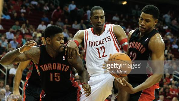 Dwight Howard of the Houston Rockets battles for the ball with Amir Johnson and Rudy Gay of the Toronto Raptors at Toyota Center on November 11 2013...