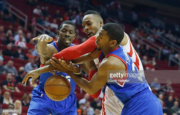 Dwight Howard of the Houston Rockets battles for the basketball against Henry Sims and Hollis Thompson of the Philadelphia 76ers during their game at...