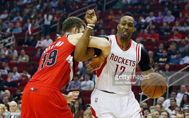 Dwight Howard of the Houston Rockets battles with the basketball against Joel Freeland of the Portland Trail Blazers during their game at the Toyota...
