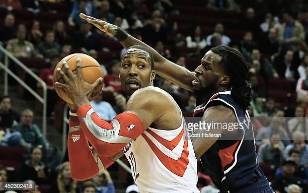 Dwight Howard of the Houston Rockets drives against DeMarre Carroll of the Atlanta Hawks at Toyota Center on November 27 2013 in Houston Texas NOTE...