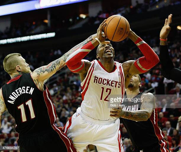 Dwight Howard of the Houston Rockets drives to the basket between Chris Andersen and Michael Beasley of the Miami Heat at Toyota Center on March 4...