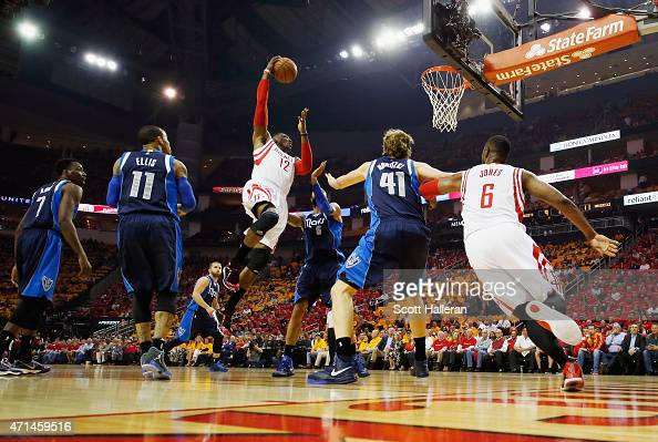 Dwight Howard of the Houston Rockets drives to the basket in front of Monta Ellis Tyson Chandler and Dirk Nowitzki of the Dallas Mavericks during...