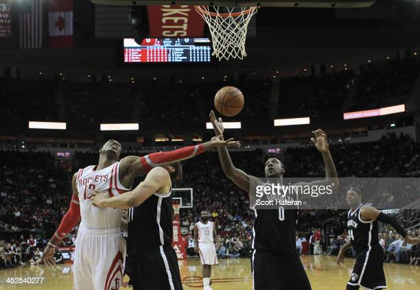 Dwight Howard of the Houston Rockets fights for a rebound with Brook Lopez and Andray Blatche of the Brooklyn Nets during the game at Toyota Center...