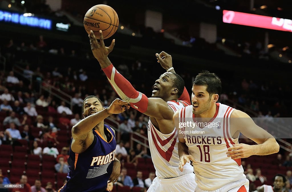 Dwight Howard #12 of the Houston Rockets grabs a rebound from Marcus Morris #15 of the Phoenix Suns during the game at Toyota Center on December 4, 2013 in Houston, Texas.