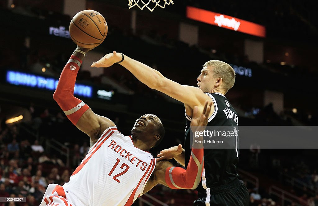 Dwight Howard #12 of the Houston Rockets is fouled by Mason Plumlee #1 of the Brooklyn Nets during the game at Toyota Center on November 29, 2013 in Houston, Texas.