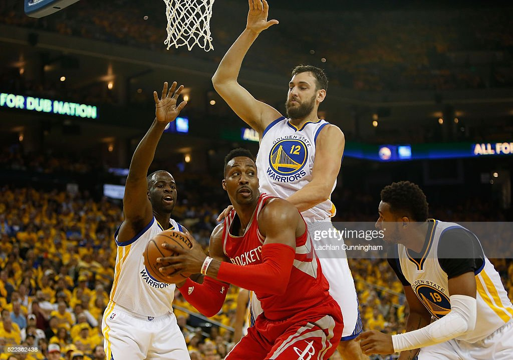 Dwight Howard of the Houston Rockets is guarded by Draymond Green Andrew Bogut and Leandro Barbosa of the Golden State Warriors in the first quarter...