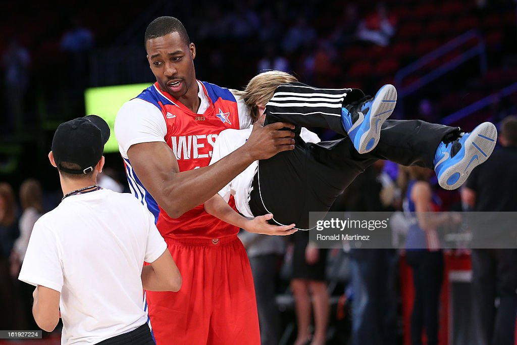 Dwight Howard of the Los Angeles Lakers and the Western Conference picks up ball kid Steven McNair as he talks to another ball kid before the 2013...