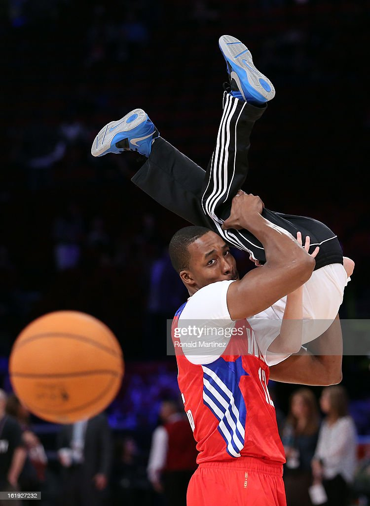 Dwight Howard #12 of the Los Angeles Lakers and the Western Conference picks up ball kid Steven McNair before the 2013 NBA All-Star game at the Toyota Center on February 17, 2013 in Houston, Texas.