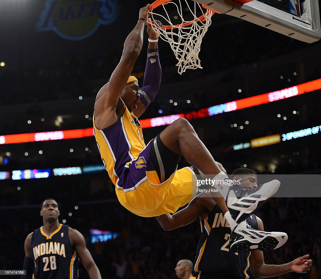 Dwight Howard #12 of the Los Angeles Lakers dunks in front of Paul George #24 and Ian Mahinmi #28 of the Indiana Pacers at Staples Center on November 27, 2012 in Los Angeles, California.